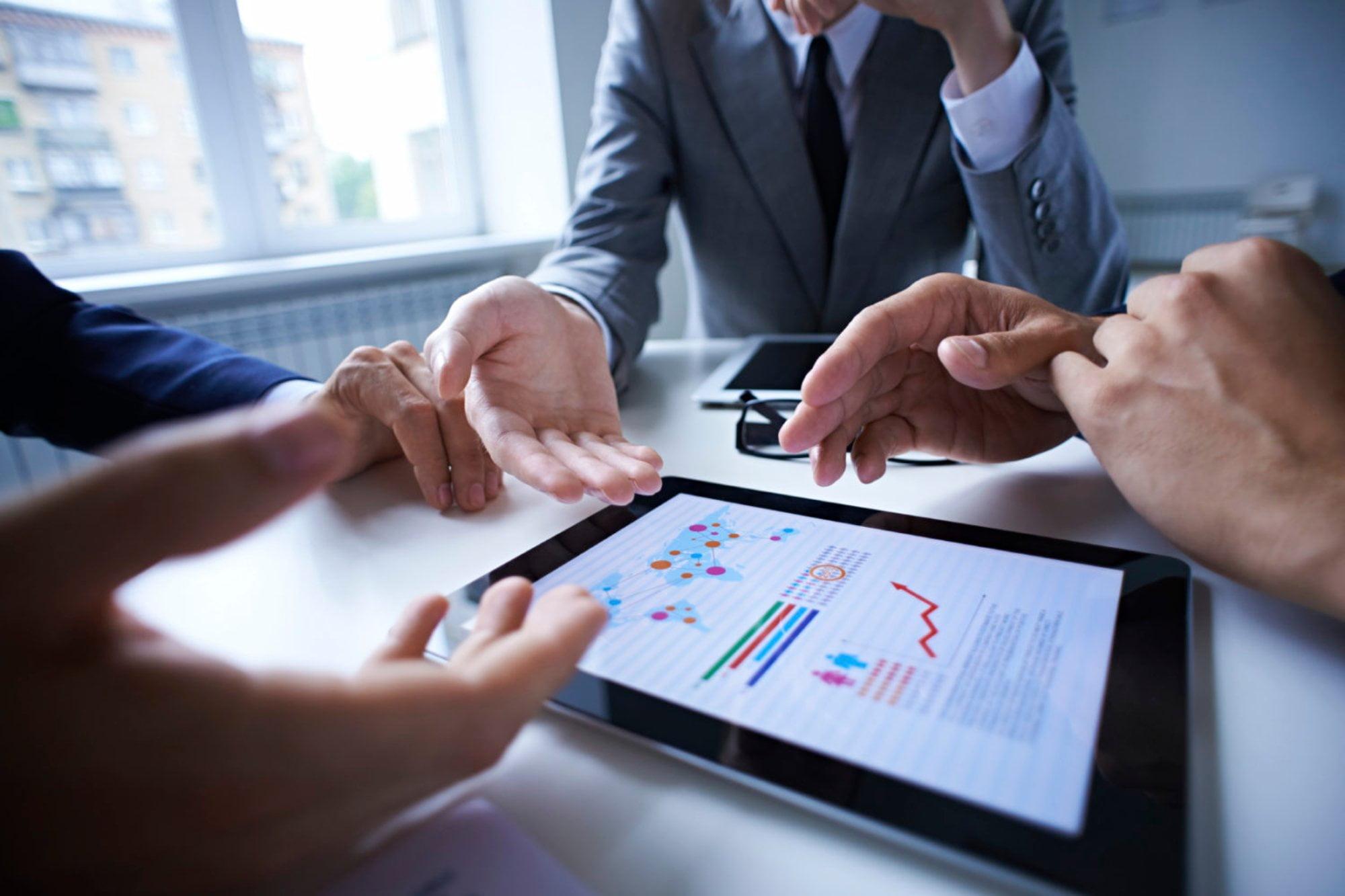 Pessoas reunidas analizando gráficos em um tablet | Marketing digital sem planejamento pode trazer prejuízos às empresas