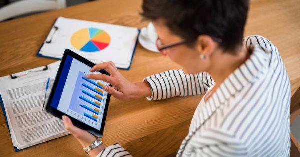 Mulher analisando gráficos em tablet   Marketing digital: setores tradicionais da economia migram para web