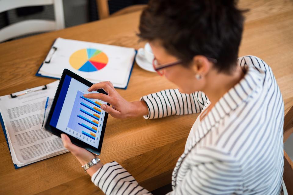 Mulher analisando gráficos em tablet | Marketing digital: setores tradicionais da economia migram para web