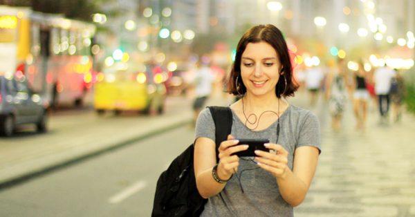 Mulher usando smartphone na Orla de Copacabana   Marketing digital: crescimento mobile no Brasil