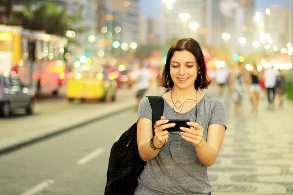 Mulher usando smartphone na Orla de Copacabana | Marketing digital: crescimento mobile no Brasil