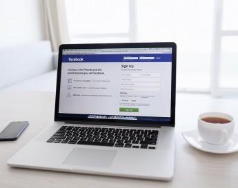 Página de login do Facebook em um notebook entre um iPhone e uma xícara | Novidade no Facebook: anúncios mobile e posts patrocinados
